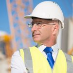 Confident construction engineer in hardhat with arms crossed on chest